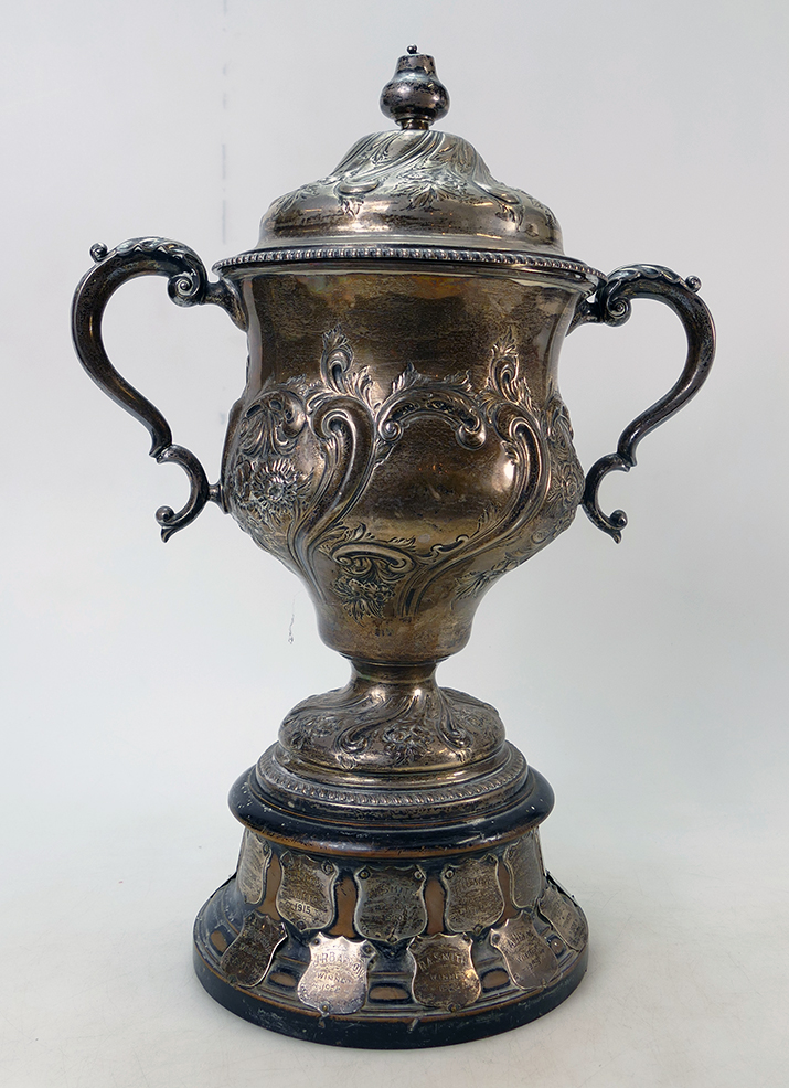 A large embossed silver twin Handled trophy. Trophy with Meir Golf Club script to central panel, mounted on original plinth with trophy shields dating to 1930. Sheffield 1906, 1467.3 grams, height on plinth 47cm. Misshapen body and dent to knob on lid.